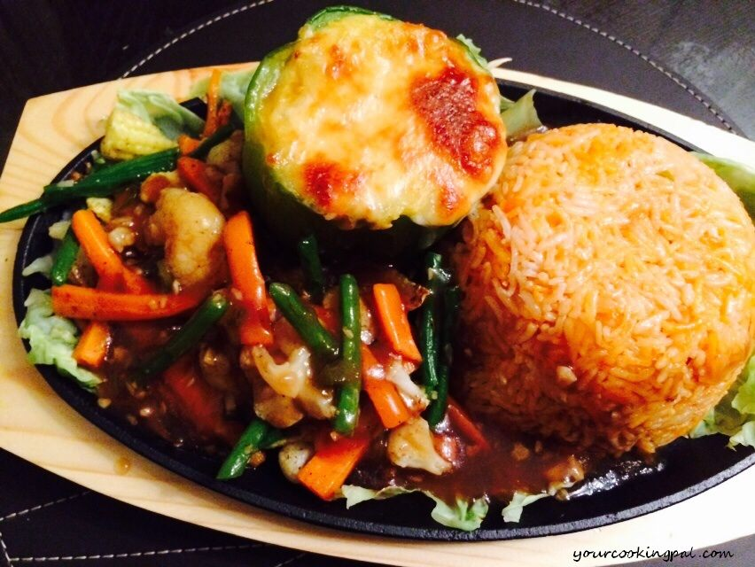 Veg sizzlers  (stuffed cheesy capcicum, Garlic sauted  veggies, tangy rice and soya chilly sauce)